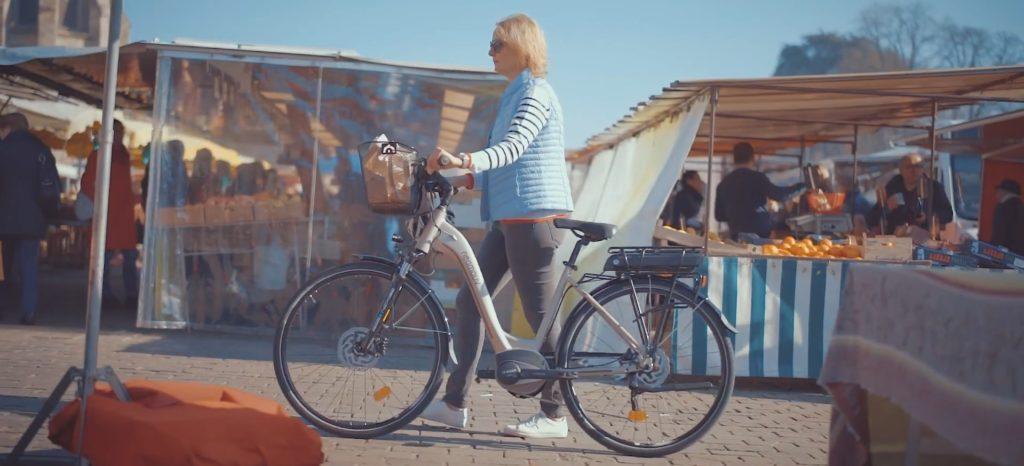 femme avce velo electrique au marché